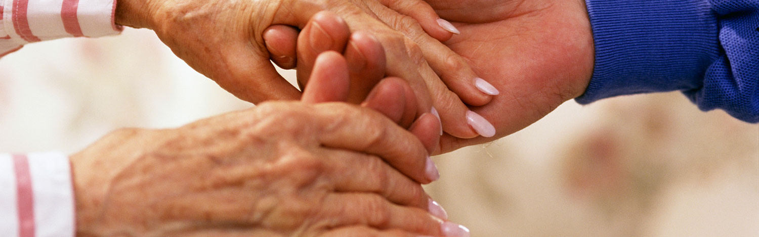 Photo of a person holding a senior's hands